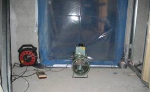 Fläkt och manometer monterade i dörr mot trapphus.